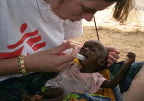 Imagem de mulher dando água em seringa para criança africana